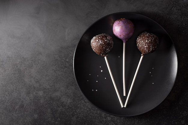 Appetizing cake pops with sparkles on a dark plate. dark food wall. horizontal image. copy space. flat lay