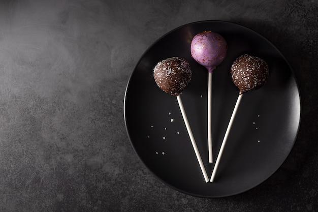 Аппетитный торт всплывает с блестками на темной тарелке. темная пищевая стена. горизонтальное изображение. копировать пространство. плоская планировка