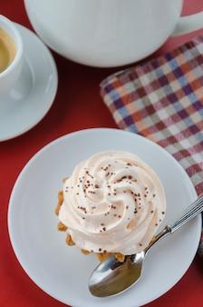 赤いテーブルにピンクのクリームで食欲をそそるケーキ