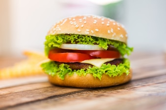 Appetizing cheeseburger on wooden table