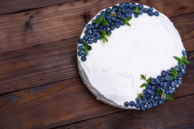 食欲をそそるチーズケーキビスケットの枕は、白いクリームブルーベリーとミントが素朴な木製のテーブルの上に立っています。皿の上の部分と甘いケーキ