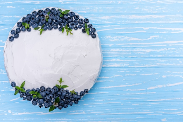 Appetizing cheesecake biscuit pillow decorated white cream blueberries and mint stands on wooden blue rustic table. sweet cake with piece on plate