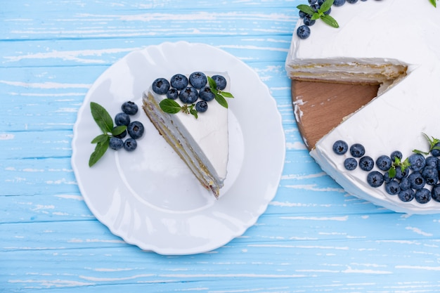 Appetizing cheesecake biscuit pillow decorated white cream blueberries and mint stands on wooden blue rustic table. sweet cake with piece and spoon on plate