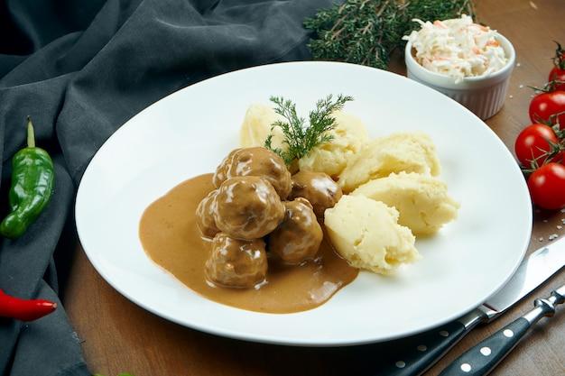食材と組成の木製のテーブルの白いプレートにマッシュポテトのおかずが入ったソースで食欲をそそるチキンミートボール