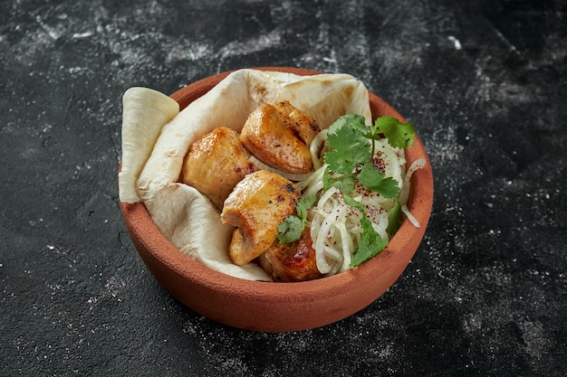 Аппетитный куриный шашлык или кебаб с маринованным луком и лавашем в керамической миске на темном столе