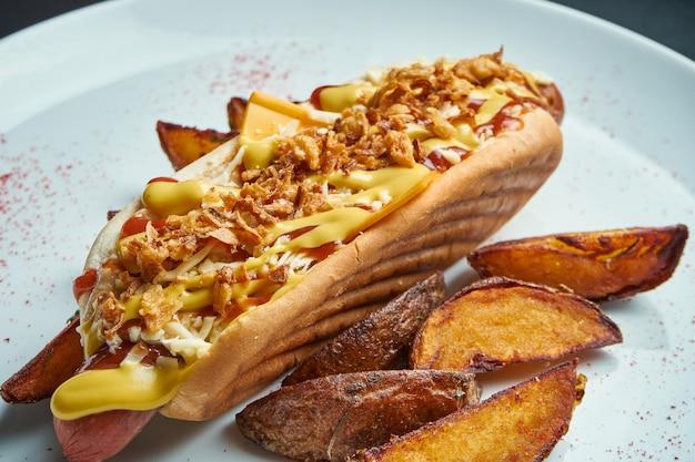 Аппетитный классический американский хот-дог с карамелизированным луком, сыром чеддер, горчицей и кетчупом с гарниром из картофеля. быстрое питание