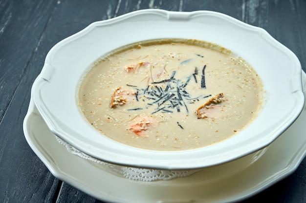 Аппетитный кокосовый суп с лососем, нори и кунжутом, подается в белой тарелке на столе из темного дерева
