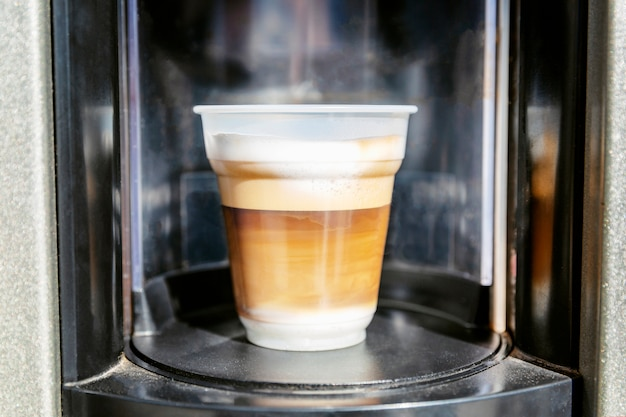 Appetizing coffee in a plastic cup from the machine. close-up.