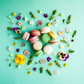 緑の背景に色とりどりのマカロンと美しい花を食欲をそそる。フラットレイアウト