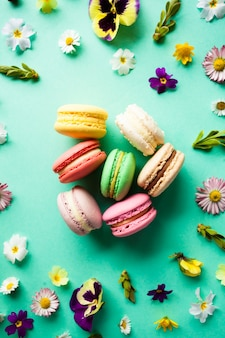 Appetizing colorful macaroons and beautiful flowers on green background. flat layout