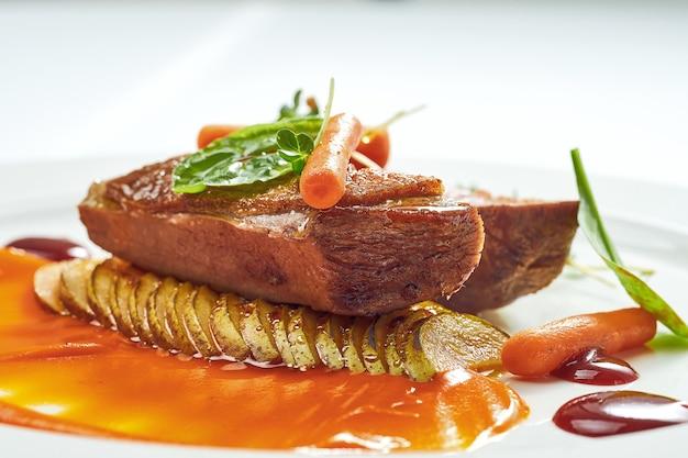 Аппетитный конфи из утиной грудки с пюре из груши и желтого яблока, ягодный соус в белой тарелке. изолированные на серой поверхности.