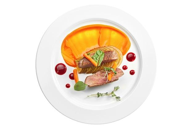 Аппетитный конфи из утиной грудки с пюре из груши и желтого яблока, ягодный соус в белой тарелке. изолированный на белой поверхности. вид сверху