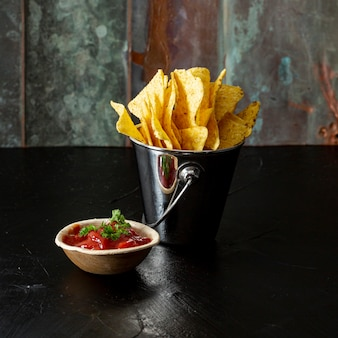 Appetizing corn chips and salsa sauce on table