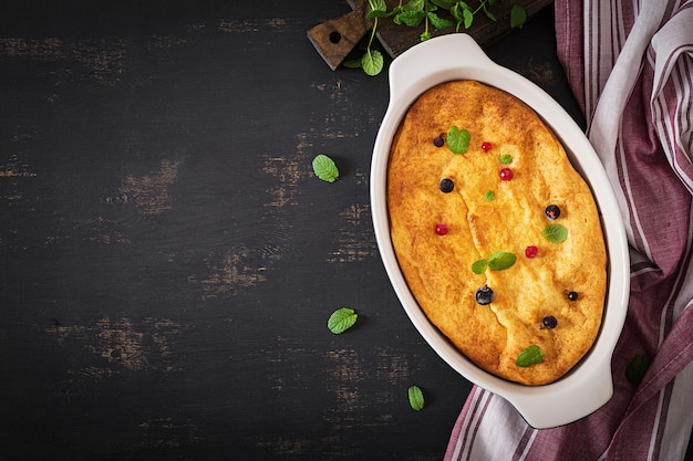 Appetizing cottage cheese casserole on dark table