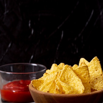 Appetizing crispy nachos with red sauce