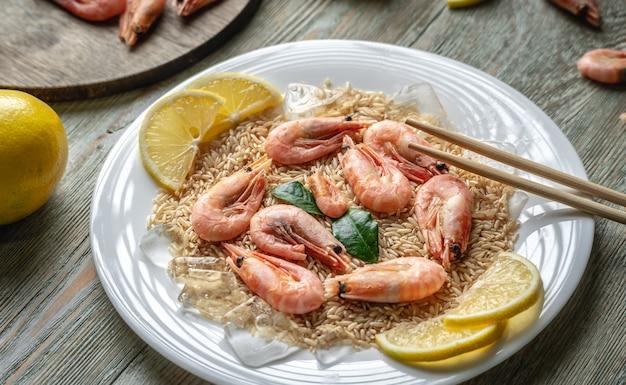 Аппетитное вкусное замороженное блюдо из креветок и риса с лимоном на деревянном столе