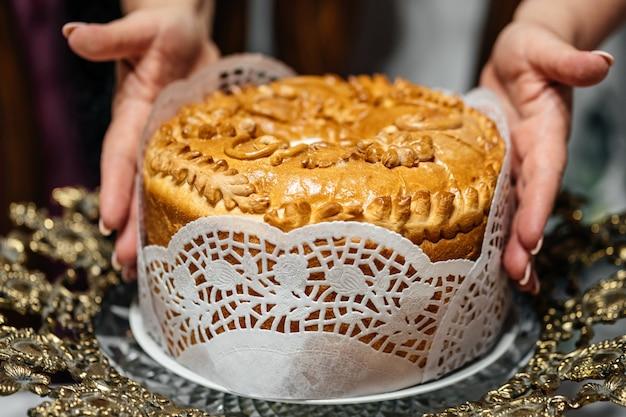 Аппетитный вкусный свадебный каравай в женских руках. свадебный хлеб для встречи молодоженов.