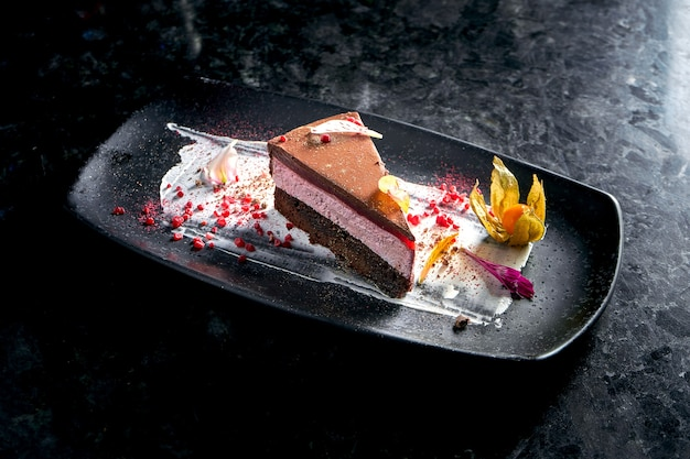食欲をそそるデザート-暗い大理石のテーブルの上の黒いプレートで提供されるチョコレートラズベリーケーキのスライス。ペストリー