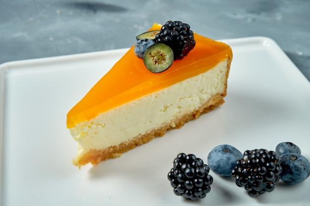 食欲をそそるデザート-カラメルとベリーの白い皿にチーズケーキ。おいしいペストリー