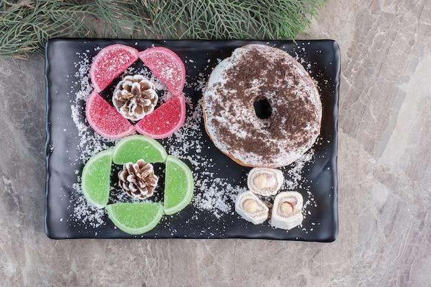 Piatto da dessert appetitoso accanto a foglie di cipresso su marmo.