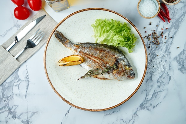Appetizing and dietary grilled dorado, served in a white plate on a marble surface