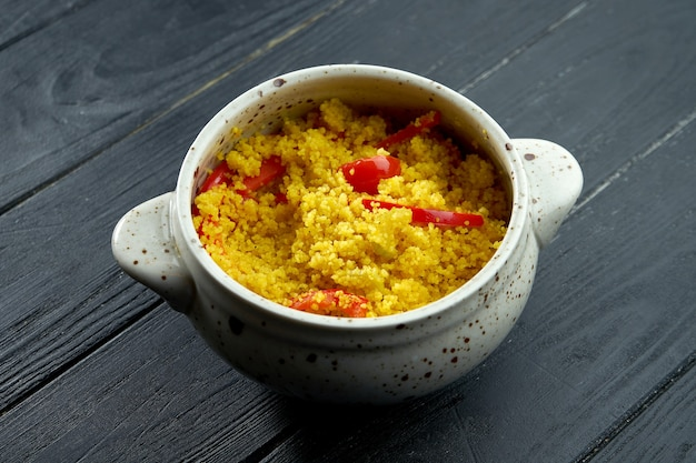 Appetizing and dietary oriental side dish - couscous porridge with vegetables served in a white pot on a black wooden background.
