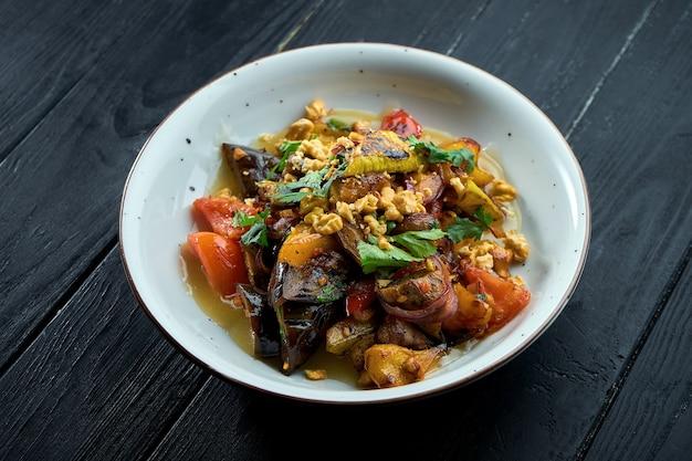 흰 접시에 소스와 견과류를 넣은 구운 야채 (토마토, 고추, 가지)의 식욕을 돋우는식이 샐러드