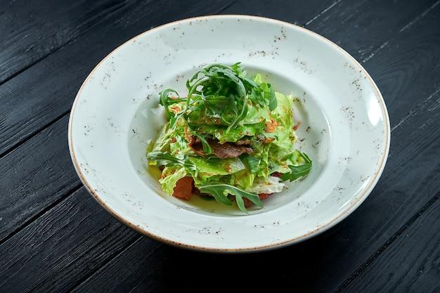 ダークウッドの背景に白いプレートにルッコラ、ソース、レタス、温かい牛肉を添えた食欲をそそるダイエットサラダ。