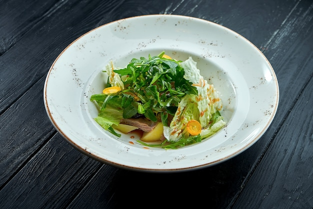 Appetizing, dietary salad with arugula, sauce, lettuce and warm beef in a white plate on a dark wood background.
