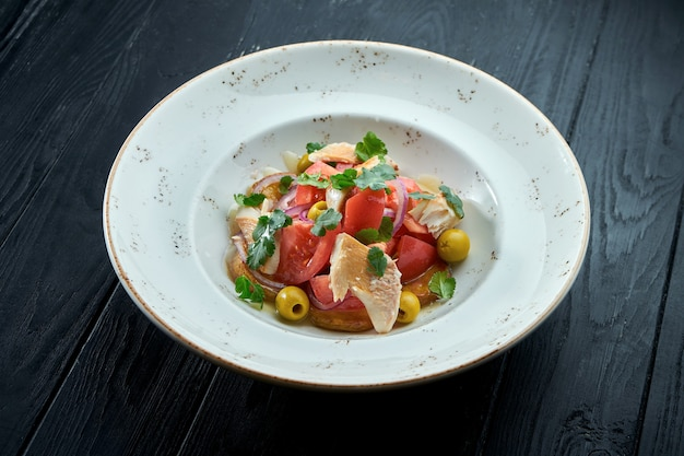 Аппетитный диетический салат с помидорами, луком, оливками и форелью на гриле в белой тарелке на темном деревянном фоне.