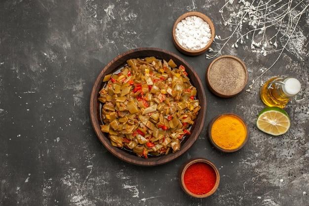食欲をそそる料理サヤインゲンとトマトの食欲をそそる料理は、暗いテーブルの上に4つのスパイスボトルのオイルと半分のライムの隣にあります
