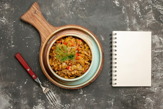 黒いテーブルのまな板の食欲をそそるインゲンとトマトの横にある食欲をそそる皿フォーク白いノート