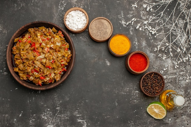 食欲をそそる料理食欲をそそるサヤインゲンとトマトの茶色のプレートの横にあるカラフルなスパイスと黒コショウの半分のレモンとオイルのボトルの4つのボウル