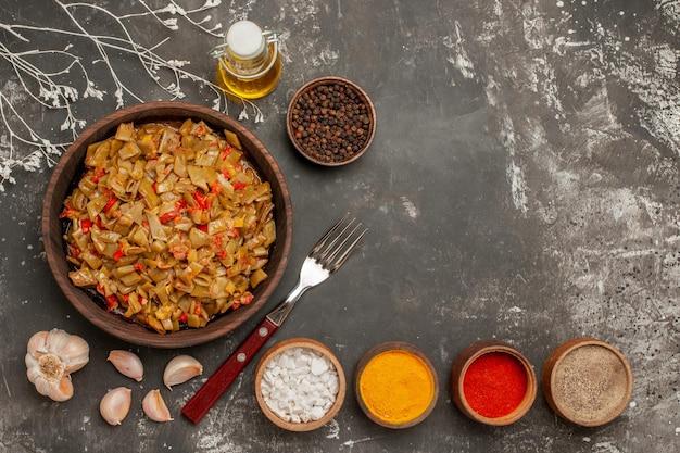 Piatto appetitoso fagiolini nel piatto accanto alla forchetta forchetta aglio e ciotole di spezie colorate sul tavolo scuro