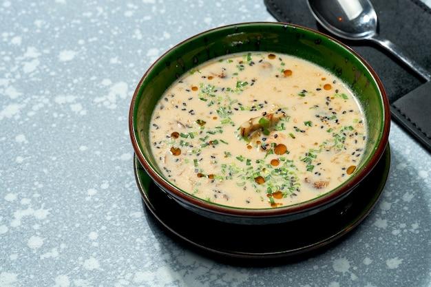 Аппетитное блюдо паназиатской кухни - сырный мисо-суп в зеленой миске на сером фоне