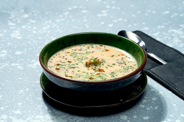 Аппетитное блюдо паназиатской кухни - сырный мисо-суп в зеленой миске на серой поверхности