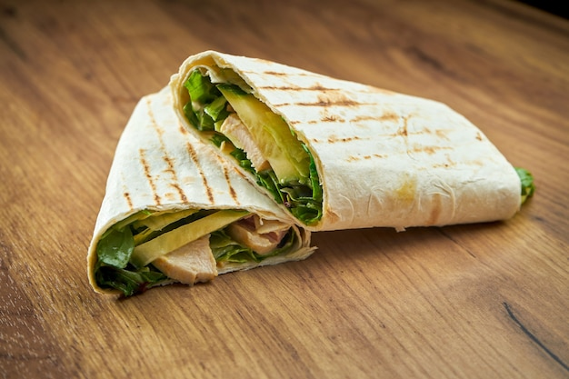 木製のテーブルで提供されるピタパンに野菜、ソース、チキンを添えた食欲をそそるドネルケバブ