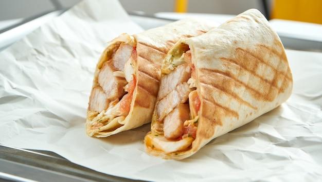 野菜、ソース、豚肉のピタパンを添えた食欲をそそるドネルケバブを紙に光で添えて
