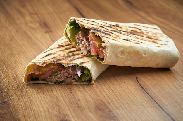 Аппетитный донер-ролл с овощами, соусом и телятиной в лаваше, подается на деревянной поверхности. традиционная уличная еда - шаурма