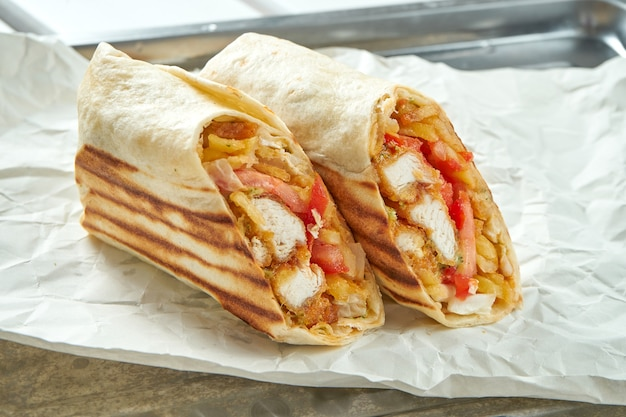 Appetizing doner roll with vegetables, sauce and chicken nuggets in pita bread, served on paper on light Premium Photo
