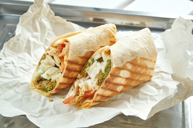Appetizing doner roll with vegetables, sauce and falafel in pita bread, served on paper on light