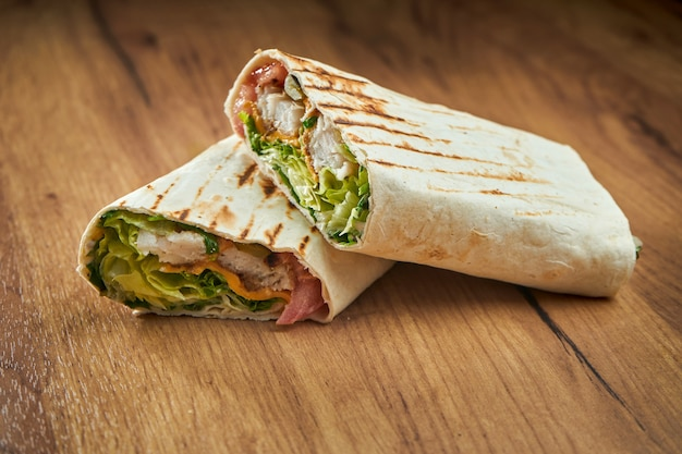 Appetizing doner roll with vegetables, sauce and fried fish makrel in pita bread, served on paper on wood