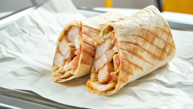 Appetizing doner roll with vegetables, sauce and pork in pita bread, served on paper on light