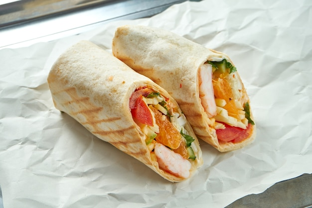 Appetizing doner roll with vegetables, sauce and shrimp in pita bread, served on paper on light