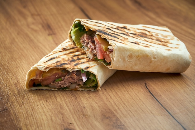 Appetizing doner roll with vegetables, sauce and veal in pita bread, served on wooden surface. traditional street food - shawarma
