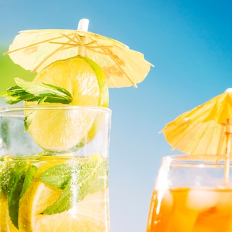 Appetizing drink with sliced lime and mint sprigs  in umbrella decorated glass