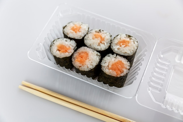 Appetizing fish rolls in a plastic container. traditional asian food.