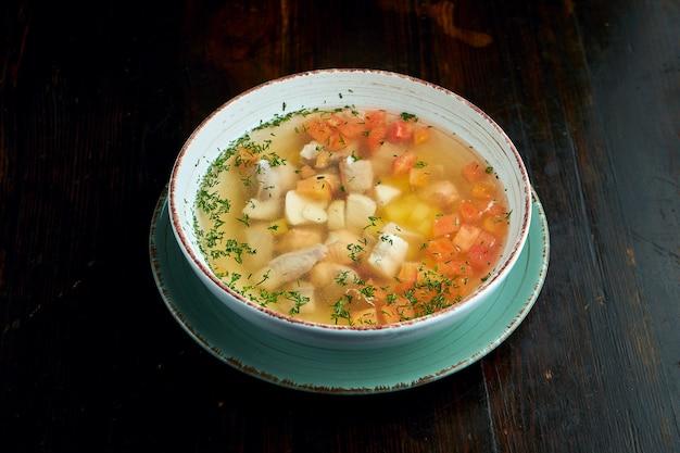 Аппетитный рыбный суп с лососем, помидорами и картофелем в миске на деревянной поверхности