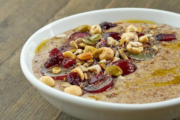 Аппетитная каша из льняного семени с оливковым маслом, семенами, виноградом и лесными орехами в белой миске на деревянном столе
