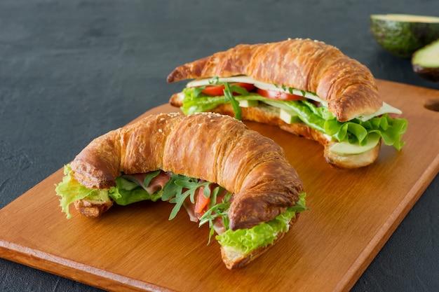 Аппетитные французские бутерброды с круассаном с лососем, авокадо, шпинатом и салатом, которые подаются на деревянном столе на сером фоне. вкусная еда на завтрак.